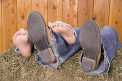 Feet and boots on hay Stock Images