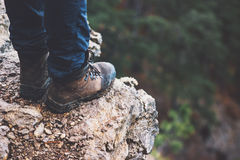 Feet boots on rocky cliff with forest aerial view Royalty Free Stock Image