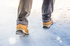 Feet in boots walking on the snow Stock Photos