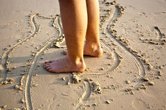 Feet of a boy is painting figures. In the fine sand of the beautiful beach stock images