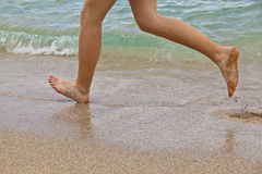 Feet of boy running along the beach. In the water Royalty Free Stock Photo