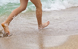Feet of boy running along the beach Stock Photos