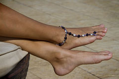 Feet with bracelet on ankle Stock Photos