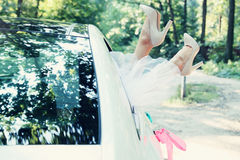Feet of the bride in the car, tinted. Bride put legs in car window, tinted Stock Photography