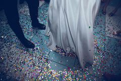 Feet of the bride and groom on a background of confetti royalty free stock images