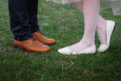 Feet of bride and groom on the background of green grass Royalty Free Stock Image