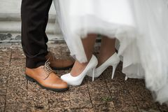 Feet of the bride and groom in an expensive-looking shoes on the asphalt road in a summer day. The image of walking newlyweds stock images