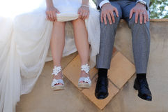 Feet of bride and groom sitting on a concrete wall Royalty Free Stock Photography