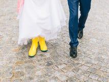 Feet of the bride and groom walk in rainy weather. Beautiful Wedding couple in the rain, walk under the rain Stock Photos
