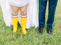 Feet of the bride and groom walk in rainy weather. Beautiful Wedding couple in the rain, walk under the rain Stock Photo