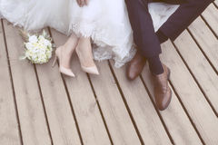 Feet of bride and groom, wedding shoes (soft focus). Cross proce. Ssed image for vintage look Royalty Free Stock Photo