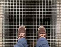 Feet with brown shoes on standing on the on the metal lattice under which is the Elevator shaft Stock Photo