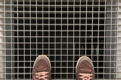 Feet with brown shoes on standing on the on the metal lattice under which is the Elevator shaft Stock Photos