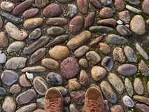 Feet in brown sneakers on the old medieval stone pavement. Royalty Free Stock Images