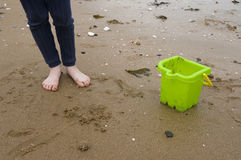 Feet and bucket. Close-up of a pair of children's feet on the beach alongside a green bucket Stock Photo