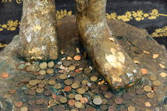 Feet of buddha image and forecast coins. Believability royalty free stock image