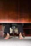 Feet of businessman under desk Stock Photography