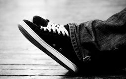 Feet and canvas shoes. Details of feet wearing black and white tennis or canvas shoes Stock Images