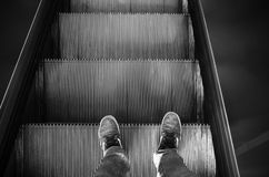 Feet in canvas shoes stand on escalator Royalty Free Stock Photos