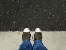 Feet in canvas shoes standing on asphalt aligned with road markings Royalty Free Stock Photos