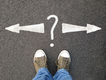 Feet standing on asphalt with arrows pointing left and right with question mark royalty free stock photos
