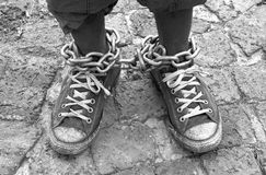 Feet in chains. Top view on two chained black feet with old dirty shoes of a South African Xhosa man standing on pavement. Image in black and white