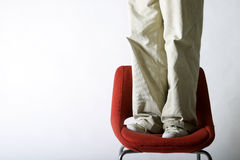 Feet on a Chair. A pair of feet on a red chair Royalty Free Stock Image