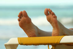Feet on the chaise. Close-up of the female feet resting on the chaise stock photography