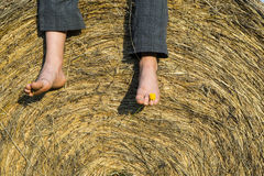 Feet of child boy sitting on haystack. / hay bale, summer, relaxing Stock Photos