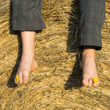 Feet of child boy sitting on haystack. / hay bale, summer, relaxing Royalty Free Stock Images
