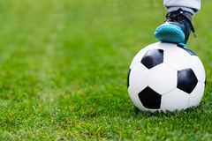 Feet of child on football / soccer ball on grass. Royalty Free Stock Images