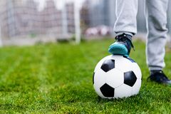 Feet of child on football / soccer ball on grass Royalty Free Stock Images