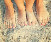 Feet of child and mom. In the sea sand Royalty Free Stock Photo