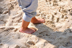 Feet of a child on sand. A child's is walking and playing on sand, feet and legs is photoed Royalty Free Stock Images