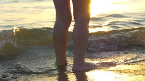 Feet of the child stand on the sea beach, in the incoming waves, against the background of the sunset. The feet of the child stand on the sea beach, in the stock video