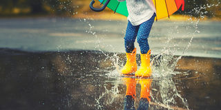 Feet of  child in yellow rubber boots jumping over  puddle in ra Royalty Free Stock Photography