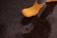 Feet of child in yellow rubber boots jumping over a puddle in th royalty free stock photos