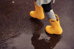 Feet of child in yellow rubber boots jumping over a puddle in th stock images