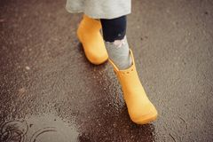 Feet of child in yellow rubber boots jumping over a puddle in th royalty free stock images