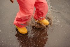 Feet of child in yellow rubber boots jumping over a puddle in th stock image