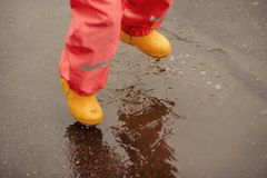 Feet of child in yellow rubber boots jumping over a puddle in th stock photography