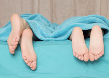 Feet of children lying on the bed Royalty Free Stock Image