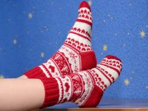 Feet with christmas socks on the desk at home Stock Photo