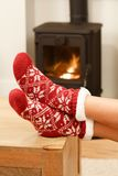 Christmas socks on womans feet. Woman warming feet in front of a cosy fire at Christmas time Stock Photo