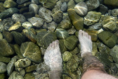 Feet in clear water. Feet in clear sea of water full of stones Stock Photos