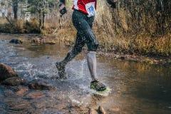 Feet closeup male runner crossing river on rocks Royalty Free Stock Image