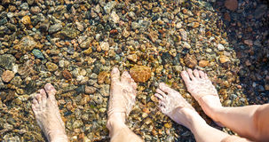 Feet in cold water Stock Photos