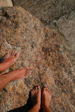Feet of couple. On a rock in the sun. The stone shines through the crystals Royalty Free Stock Photo