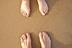 Feet of a couple at the beach Stock Image