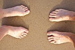 Feet of a couple at the beach Stock Photos